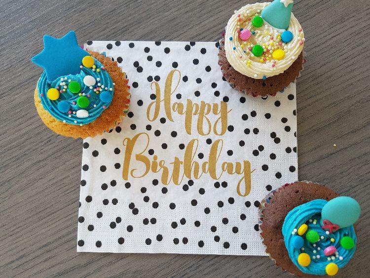 verjaardagscupcakes met blauwe en witte botercrème afgewerkt met suikerdecoratie