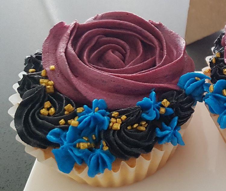 cupcake met paarse botercrème in de vorm van een bloem